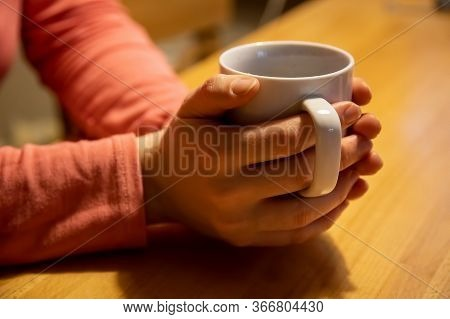 Closeup Female Hands Hold And Hug A White Cup With A Warm Drink On A Wooden Table. The Concept Of Co