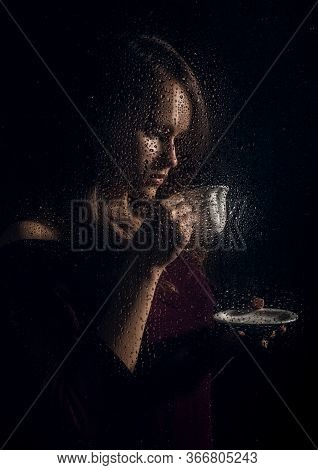 Nice Young Girl Drinks Coffee Behind The Wet Glass, Raindrops On Glass