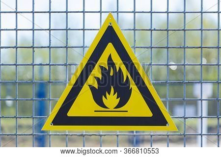 Black Caution Or Warning Fire Triangle Sign On Yellow Background Or Table On The Painted Grill Of St