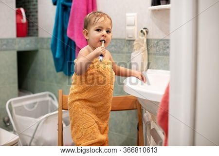 Little Cute Baby, 1, 3 Year Old, Is Standing On A Chair In The Bathroom Wrapped In An Orange Towel W