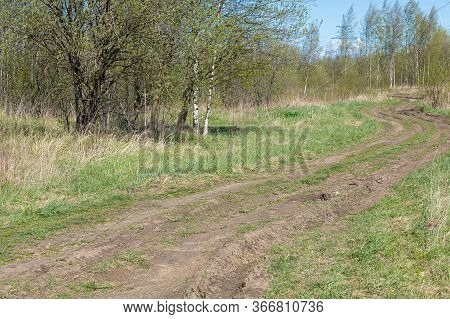 Unpaved Road Among Spring Landscape With Trees,bushes And Grass With Mud And Slush