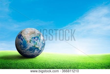 Ecology And Environment Concept : Blue Planer Earth On Green Grass Meadow Field With Blue Sky In Bac
