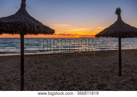 Beach umbrellas at Arenal beach near Palma de Mallorca in sunset time. Mallorca island, Spain Mediterranean Sea, Balearic Islands.