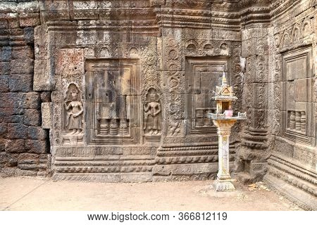 Wall carving with woman dancer apsara and traditional small spirit's house in Nokor Bachey Pagoda (Wat Nokor), Kampong Cham, Cambodia