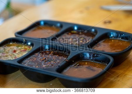 The Spicy Sauces And Condiments For Shabu In Cup Of Sauce On A Wooden Table Background.dipping Sauce