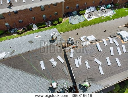 A Worker Replace Shingles On Repairing The Roof Of A Home A Renovation Roof Covering