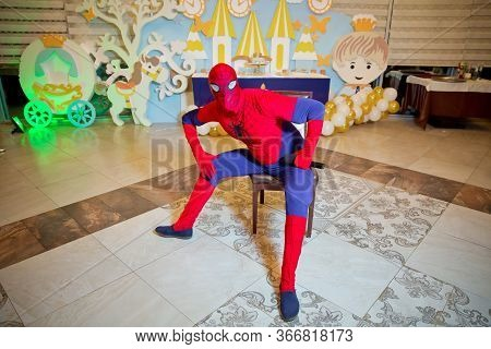 Spider-man Model Display Sitting On The Table . A Boy Dressed As A Spiderman Sits At A Table . Baku,