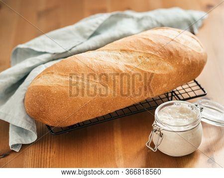 British White Bloomer Or European Sourdough Baton Loaf Bread On Wooden Background. Fresh Loaf Bread