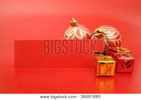 Xmas ornaments and tag on red background.
