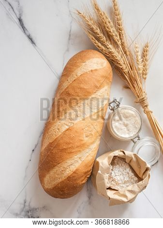 British White Bloomer Or European Sourdough Baton Loaf Bread On White Marble Background. Fresh Loaf