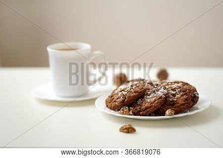 Oatmeal Cookies On A White Table On A White Plate, Several Pieces Decorated With White Coconut Shavi