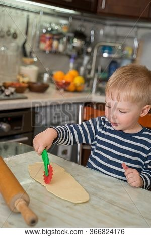 Little Cute Blond Boy In Kitchen Is Learning To Cut Flour Dough With Childrens Shaped Baking Knife.
