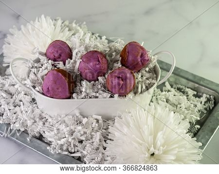 Purple Decorated Cinnamon Roll Cake Pop Balls Piled In A White Tin Bucket With White Paper Shreds On
