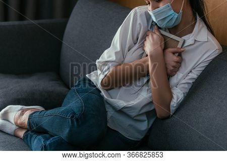 Cropped View Of Depressed Young Woman In Medical Mask Grieving While Holding Photo Frame Near Chest