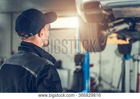 Caucasian Male Worker Inspecting Car Hoisted On Hydraulic Lift In Automotive Workshop.