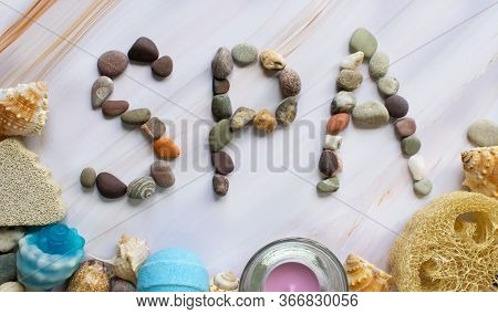 Inscription Spa Made Of Stones On A Marble Surface. Shells, Soap, Candle, Bath Bomb, Loofah, Pumice