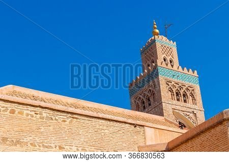 Terracotta Walls And Minaret Of Koutoubia Mosque In Marrakesh, Morocco. Oriental Architecture Agains