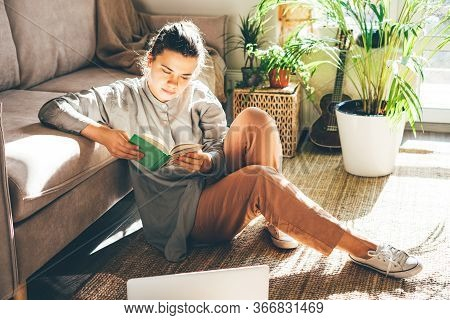 Young Beautiful Woman Works From Home. Sits On The Floor. Read Notes In Notebook At Sunny Room.