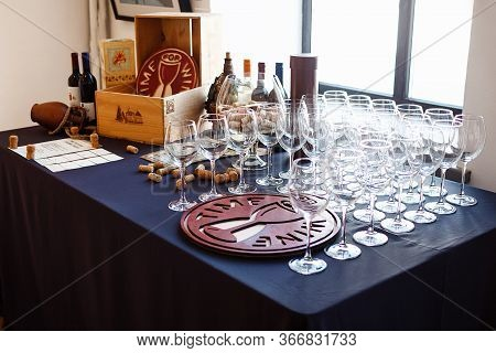 On The Table With A Blue Tablecloth By The Window There Are A Lot Of Wine Glasses, A Bottle And A Ju
