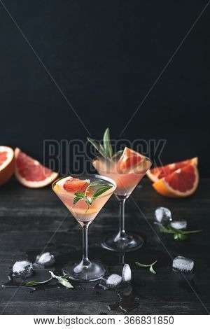 Blush Grapefruit And Sage Gimlet In Glasses, Standing On A Dark Wooden Table