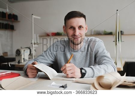Smiling Man Doing Engineering Or Managing Work At A Generic Workshop. Local Small Business, Clothing