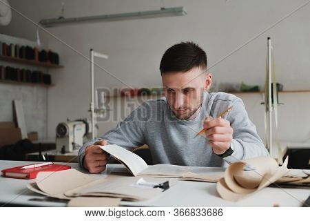 Man Doing Engineering Or Managing Work At A Generic Workshop. Local Small Business, Clothing Designe