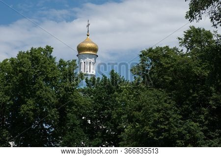 The Dome Of The Orthodox Church Over The Trees. Golden Dome Against The Blue Sky.