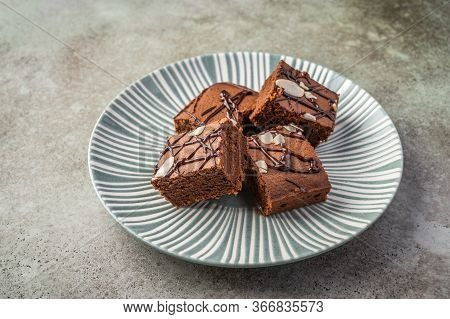 Homemade Brownies With Almond Petals On A Textured Plate On A Wooden Background. Close Up. Horizonta