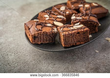 Homemade Brownies With Almond Petals On A Dark Plate On A Wooden Background. Close Up. Selective Foc