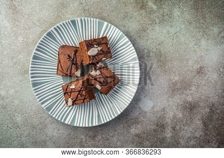 Homemade Brownies With Almond Petals On A Textured Plate On A Wooden Background. Top View. Copy Spac