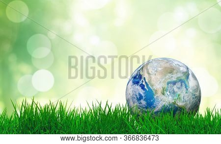 Ecology And Environment Concept : Blue Planet Earth On Green Grass With Blurry Green Natural And Sun