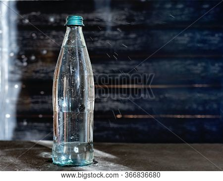 Glass Bottle Of Mineral Water On Grey Table. Sparkling Water In A Glass Bottle With Air Bubbles And
