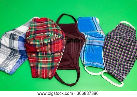 Different Colors Of Washable Face Masks On Green Background. Fashionable Face Masks Reusable And Was