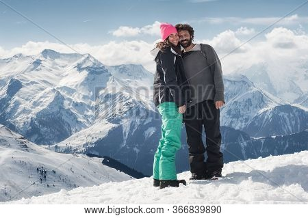 Romantic Snowboarder Couple Embracing On Snow, With Beautiful Alps Mountain Range In Background. Lov