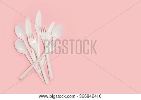 Disposable White Plastic Flatware On A Pink Background In A Top View