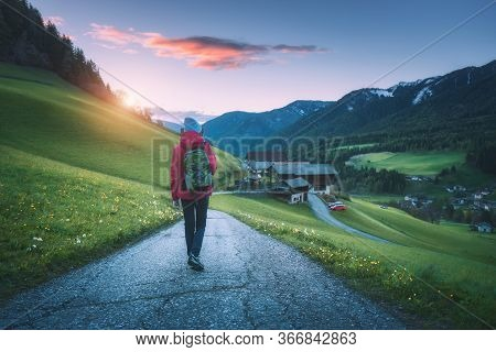 Beautiful Young Woman With Backpack Is Standing On The Mountain Road At Sunset In Autumn. Landscape