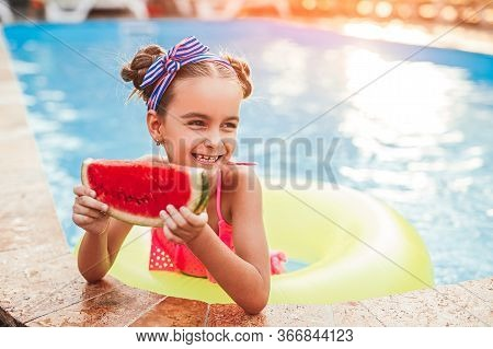 Optimistic Kid With Inflatable Ring Smiling And Looking Away While Resting In Pool And Eating Waterm