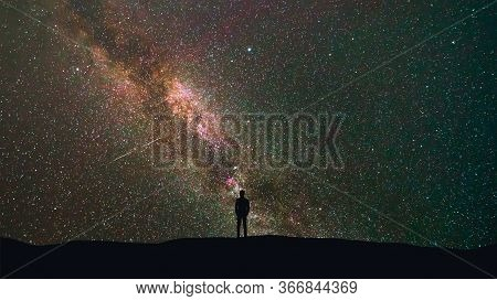 The Man Stand On A Background Of A Milky Way With Asteroids Skyfall.