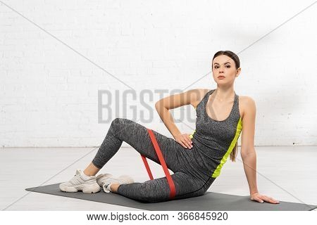 Sportive Woman With Hand On Hip Working Out With Resistance Band On Fitness Mat