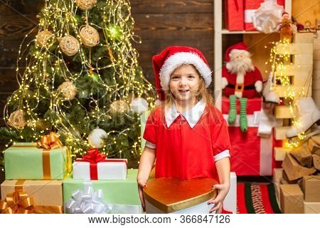 Cheerful Cute Child Opening A Christmas Present. Happy Child Decorating Christmas Tree. Cute Little
