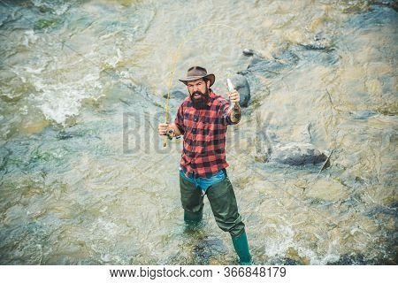 Angler Catching The Fish. Handsome Fisherman In Hat And Red Checkered Shirt. Carry On Fishing. Big G