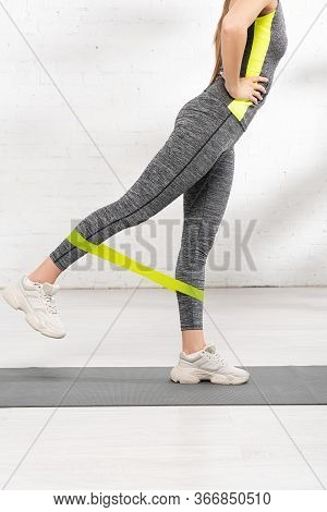 Cropped View Of Sportive Girl With Hand On Hip Exercising With Resistance Band On Fitness Mat