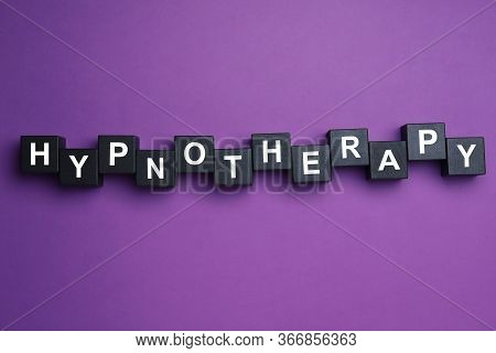 Black Wooden Blocks With Word Hypnotherapy On Purple Background, Flat Lay