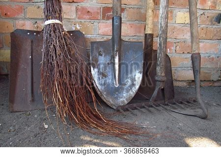 Old Garden Tools . Dirty Rusty Shovels, Garden Hoe, Rake And Broom On Brick Wall Background