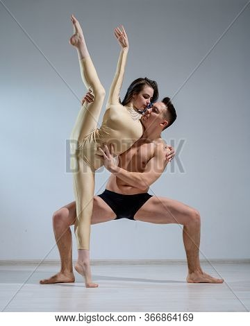 Partners Acrobats Posing Against A White Wall. Young Duet Of Ballet Dancers Perform Support With Twi