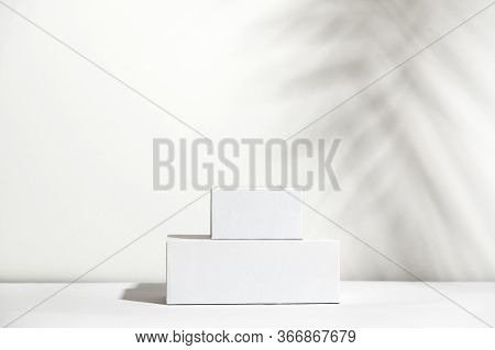 White Empty Stands On Light Shadow Background. Blank Unbranded Shopfront. Showcase For Cosmetic Prod
