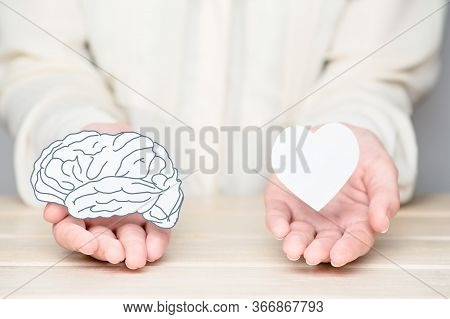 Female Hands Holding Paper Cut Brain And Soul. Conflict Between Emotions And Rational Thinking. Bala