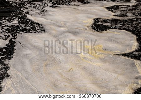 Stain Yellow Dirty Foam On The Water Man-made Pollution Of The Reservoir. The Problem Of Technogenic
