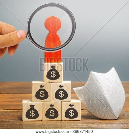Wooden Blocks With Money, Man And Protection Shield. Concept Security Of Money, Guaranteed Deposits.