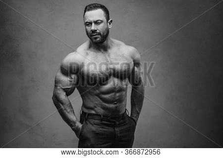 Black And White Photo Of A Strong Athlete Posing In A Dark Studio While Being Shirtless, Showing His